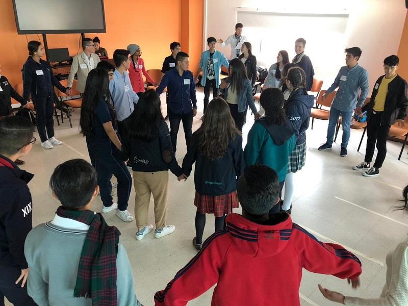Jóvenes reunidos formando un círculo